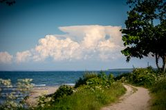 En smal bana leder till stranden från havet arkivfoto
