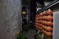 En smal gränd dekorerade med röda lyktor i Xidi, en liten forntida by i det Anhui landskapet i Kina Royaltyfri Fotografi