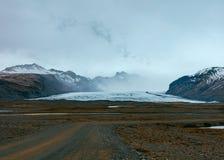 En smal väg i en öken med härliga kullar och berg i bakgrunden royaltyfri foto