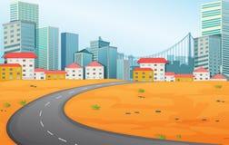 En smal väg som går till staden Arkivfoton