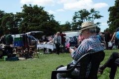 En smart äldre man ser hans moderna telefon fotografering för bildbyråer