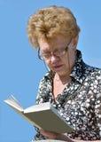 En smart kvinna med en bok Arkivfoton
