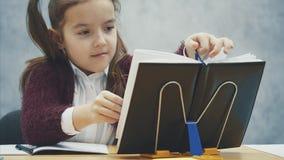 En smart skolflicka sitter på tabellen och utför en läxauppgift Under denna tid ser han i en svart bok lager videofilmer