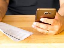 En smart telefon för maninnehav för att använda online-bankrörelsen app för att betala kreditkorträkningen Arkivbild