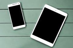 En smart telefon och en digital minnestavla på trätabellen Royaltyfria Bilder