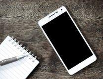 En smart telefon på trätabellen Arkivbild