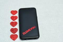 En smart telefon som visas med orden älskar jag, dig och hjärtor Fotografering för Bildbyråer