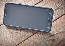 En smartphone i positionen för hållande ögonen på filmer på en trätabell Royaltyfria Bilder