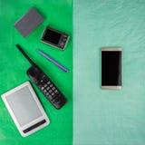En smartphone och saker, som den byter ut, p? olika halvor av enf?rgad rektangel arkivfoton