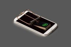 En smartphone symbolically som råttfällan med avtryckare royaltyfri fotografi