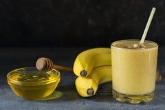 En smoothie av mango, bananen och honung på den mörka trätabellen i en glass dryckeskärl Fotografering för Bildbyråer