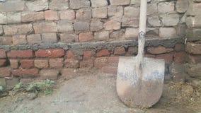 En smutsig skyffel eller spade förläggas på lerig jordning med den olden tegelstenväggen arkivbild