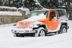 En snö täckte jeepen som parkerades på vägrenen under strängt snöfall arkivbilder