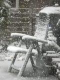 En snö täckte stol i en trädgårdträdgård arkivbild