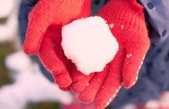 En snöboll i händerna av ett barn arkivfoton