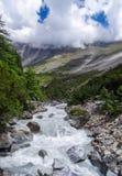 En snabb flödande flod med ett kors lutade ned slätt mountian arkivfoton