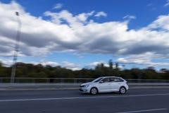 En snabb rörande bil mot bakgrunden av en härlig blå himmel och fluffiga vita moln Fotografering för Bildbyråer