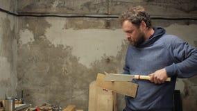 En snickare med ett skägg och mustaschsågar en träbeståndsdel som rymmer det i hand och skador ett finger lager videofilmer