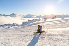En snowboarder i en skidamaskering och en ryggsäck rider på entäckt lutning som lämnar bak ett snöpulver mot Arkivfoto