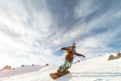 En snowboarder i en skidamaskering och en ryggsäck rider på entäckt lutning som lämnar bak ett snöpulver mot Royaltyfri Foto