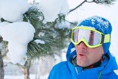 En snowboarder som har gyckel som vilar på en skidasemesterort Arkivbild