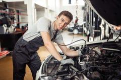 En snygg mekaniker ler, medan kontrollera en motor royaltyfria bilder