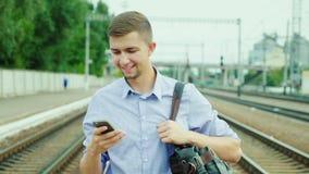 En snygg ung affärsman går vidare den järnväg plattformen Använder en mobiltelefon Begreppet är en lyckad affär lager videofilmer
