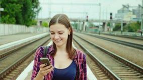 En snygg ung kvinna går vidare den järnväg plattformen Använder en mobiltelefon Begreppet är en lyckad affärstur stock video