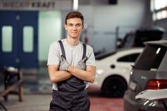 En snygg ung man står nära bilar på en bilservice arkivbild