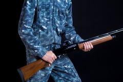 En soldat i milit?r likformig med en hagelgev?r Kriglekar F?rberedelse f?r v?ren, h?stjakt Soldat eller jägare på en svart fotografering för bildbyråer
