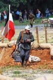 En soldat-reenactor går vid den tyska flaggan Royaltyfri Bild