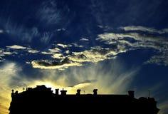 En solnedgång och en kontur av en byggnad Arkivbilder