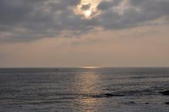 En solnedgångsikt av ett hav och en himmel Arkivbild