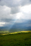 En solstråle som stiger jorden på en regnig dag Arkivfoto