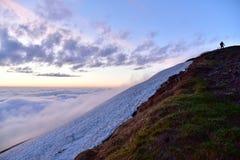 En soluppgång är ovanför moln Arkivfoto