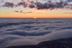 En soluppgång är ovanför moln Arkivbilder