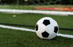 En soocer eller en fotboll på ett fält av gräsplan med mål i bakgrund fotografering för bildbyråer