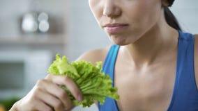 En souhaitant perdez le poids et soyez mince, dame se faisant mangeant de la laitue, nutrition banque de vidéos