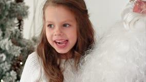 En souriant et lancez la fille partageant ses rêves de Noël avec Santa clips vidéos
