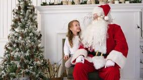 En souriant et lancez la fille partageant ses rêves de Noël avec Santa banque de vidéos