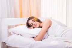 En sova kvinna ligger i säng med hennes huvud Royaltyfri Fotografi