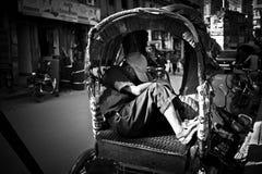 En sova Rickshawchaufför på gatorna av Katmandu, Nepal i svartvitt Arkivfoto