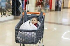 En spårvagn med produkter som barnet sitter i Full vagn med mat i supermarket I vagnen sitter en behandla som ett barn royaltyfria bilder