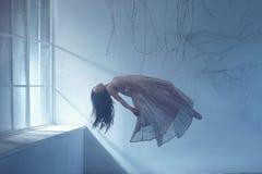 En spökeflicka med långt hår i en tappningklänning Ett fotografi av svävning som liknar en dröm Ett mörkt gotiskt rum med royaltyfri fotografi