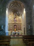 En spansk kyrklig inre med kyrkbänkar och altaret royaltyfri fotografi