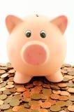 En spargris på en hög av mynt för eurocent Arkivfoto