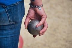 En spelare rymmer i hand en boule för petanque royaltyfri foto