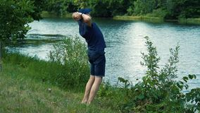 En spenslig gråhårig man i en blåa t-skjorta, lock och exponeringsglas går barfota på det gröna gräset på flodbanken på a stock video