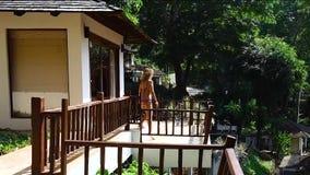 En spenslig kvinna i en färgrik randig baddräkt går på terrassen på en varm solig sommardag stock video
