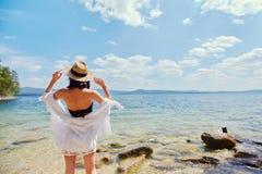 En spenslig kvinna i en vit skjorta och hatt kopplar av nära vattnet fotografering för bildbyråer